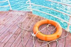 Boia salva-vidas alaranjado com corda em um cais de madeira perto do mar ilustração do vetor