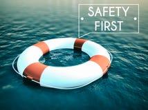 Boia salva-vidas do sinal da segurança em primeiro lugar em ondas de água áspera Foto de Stock