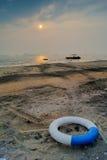 Boia salva-vidas e praia selvagem sob o por do sol Fotografia de Stock Royalty Free