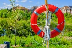 Boia salva-vidas em um fundo de casas luxuosas Imagem de Stock Royalty Free