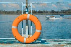 Boia salva-vidas no cais, no rio e no céu azul Imagem de Stock