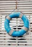 Boia salva-vidas que pendura em um fundo de madeira Fotos de Stock Royalty Free
