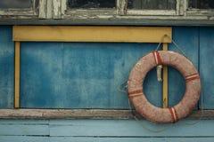 Boia salva-vidas velho em uma parede de madeira da construção Fotografia de Stock