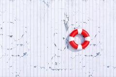 Boia salva-vidas vermelho em uma parede de madeira da prancha do grunge velho, conceito do verão Imagem de Stock