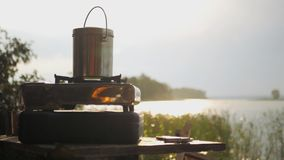 Boil in the morning on a gas stove, near a lake with beautiful sun glare on it. HD. Boil in the morning on a gas stove, near a lake with beautiful sun glare on stock photos