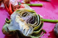 Boiled artichoke cut in half lying on pink tablecloth with mushroom and asparagus at crawfish boil - selective focus Royalty Free Stock Photo