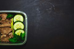 Boiled beef and pieces of fresh cucumber in a small container on a black background, top view, close up. Healthy food, diet, fitne. Ss. copy space Royalty Free Stock Photography