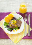 Boiled beef tongue with orange sauce. And fresh salad on white plate and color fabric Royalty Free Stock Images