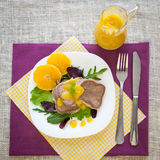 Boiled beef tongue with orange sauce. And fresh salad on white plate and color fabric Royalty Free Stock Image