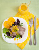 Boiled beef tongue with orange sauce. And fresh salad on white plate and yellow fabric Stock Photo