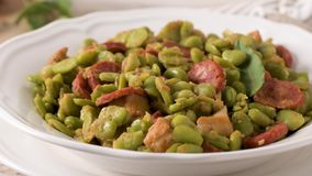 Boiled broad bean. With chorizo and laurel leaves on a white ceramic plate. Typical portuguese food stock video footage