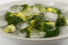 Boiled broccoli in cold water with ice cubes Royalty Free Stock Photography
