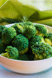 Boiled broccoli in a white bowl on a kitchen table. Healthy food: boiled broccoli in a white bowl on a kitchen table Stock Photography