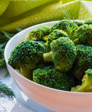 Boiled broccoli in a white bowl on a kitchen table. Healthy food: boiled broccoli in a white bowl on a kitchen table Stock Photo