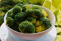 Boiled broccoli in a white bowl on a kitchen table. Healthy food: boiled broccoli in a white bowl on a kitchen table Royalty Free Stock Photography