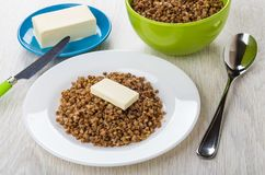 Boiled buckwheat with butter, buckwheat in bowl, butter in sauce Royalty Free Stock Photos