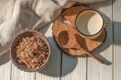 Boiled buckwheat cereal in a pottery bowl, a metal mug with milk and a wooden spoon on a rustic wooden surface decorated with a l. A photo with boiled buckwheat Stock Photo