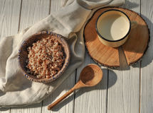 Boiled buckwheat cereal in a pottery bowl, a metal mug with milk and a wooden spoon on a rustic wooden surface decorated with a li. A photo with boiled buckwheat Stock Images