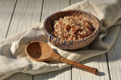 Boiled buckwheat cereal in a pottery bowl and a wooden spoon on a rustic wooden surface decorated with a linen napkin. A photo with boiled buckwheat cereal in a Royalty Free Stock Images