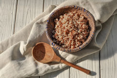 Boiled buckwheat cereal in a pottery bowl and a wooden spoon on a rustic wooden surface decorated with a linen napkin. A photo with boiled buckwheat cereal in a Stock Image
