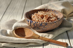 Boiled buckwheat cereal in a pottery bowl and a wooden spoon on a rustic wooden surface decorated with a linen napkin. A photo with boiled buckwheat cereal in a Royalty Free Stock Photography