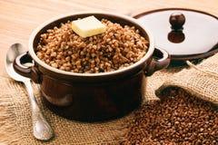 Boiled buckwheat porridge in ceramic pot on wooden background. Stock Photo