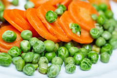 Boiled carrots and grean peas on white plate close up stock image