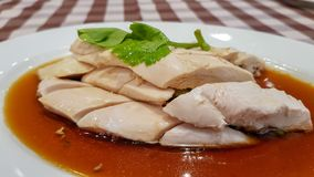 Boiled chicken Chinese style pour with gravy served in the white plate on the checker square pattern tablecloth. Boiled chicken is very famous food in Thailand royalty free stock images
