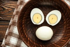 Boiled chicken eggs in clay bowl arranged in form of smiley face Stock Photography