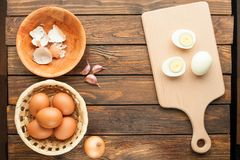 Boiled chicken eggs at cutting board decorated with food ingredi. Ents on an old wooden table Royalty Free Stock Images