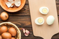 Boiled chicken eggs at cutting board decorated with food ingredi Royalty Free Stock Images