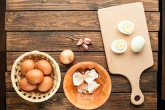 Boiled chicken eggs at cutting board decorated with food ingredi. Ents on an old wooden table Royalty Free Stock Photography