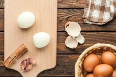 Boiled chicken eggs at cutting board decorated with food ingredi. Ents on an old wooden table Stock Photo