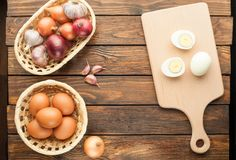Boiled chicken eggs at cutting board decorated with food ingredi. Ents on an old wooden table Royalty Free Stock Image