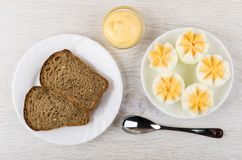 Boiled chicken eggs in saucer, bowl with mayonnaise, bread and spoon on table. Royalty Free Stock Images