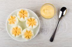 Boiled chicken eggs in saucer, bowl with mayonnaise and spoon Royalty Free Stock Image