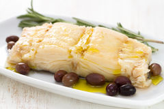 Boiled cod fish with olives Stock Photo
