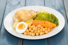 Boiled cod fish with potato, carrot, cabbage , chick-pea and egg. On plate on blue background stock image