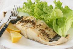 Boiled codfish with lemon. And lettuce Stock Photos