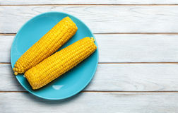 Boiled corn on blue plate on white wooden Royalty Free Stock Image