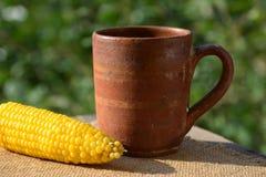Boiled corn and clay mug, still life Stock Photography