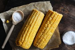 Boiled corn cob with salt on a wood Royalty Free Stock Photo