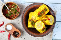 Boiled corn with hot sauce, herbs, salt and spices Stock Images