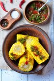 Boiled corn with hot tomato sauce, herbs, salt and spices Stock Photo