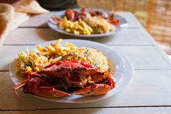 Boiled crab on wooden table,cooked crabs on white plate served with rise and french fries, top view.Seafood concept.Selective focu royalty free stock photo