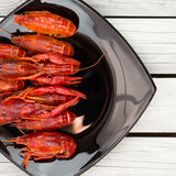 Boiled crawfish. Woden background. Rustic style. Red boiled crawfish on the black rectangular plate. Stock Photos