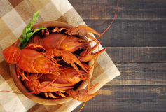 Boiled crawfishes in a round wooden plate on a wooden background Stock Photography