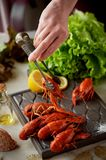 Boiled crayfish lie on a platter.Female hand holding tweezers and puts cancers. Fresh salad. Nutritious and delicious. Boiled crayfish lie on a platter. Female stock image