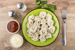 Boiled dumplings, ketchup, mayonnaise, spices and fork on wooden Royalty Free Stock Photography