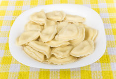 Boiled dumplings in white glass plate on yellow tablecloth Royalty Free Stock Photo